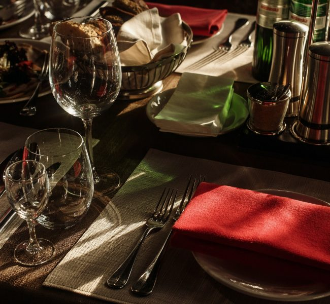 Luxury wine glasses and silver tableware near plates with red napkins